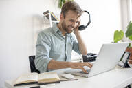 Smiling man with headphones and laptop at desk in office - VPIF01779