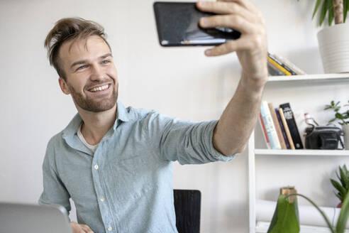 Smiling man taking a selfie at desk in office - VPIF01782