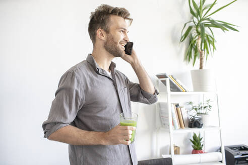 Smiling man on the phone in office - VPIF01785