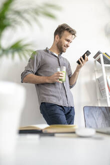 Smiling man using smartphone in office - VPIF01788