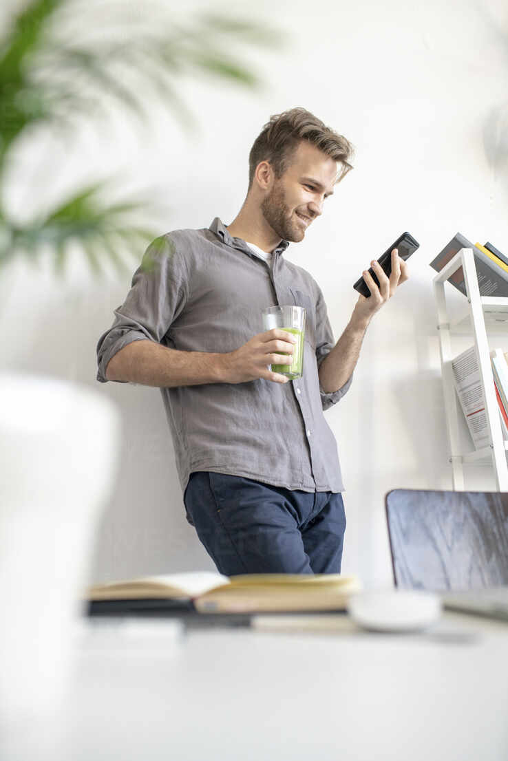Smiling man using smartphone in office - VPIF01788 - Vasily Pindyurin/Westend61
