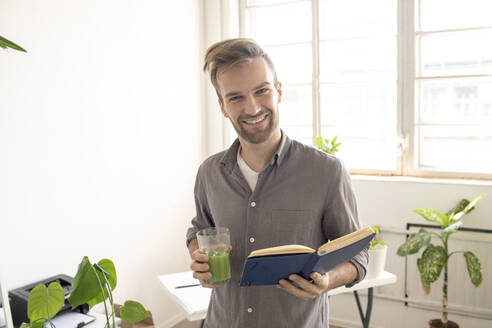 Portrait of smiling man holding book in office - VPIF01794
