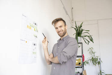 Portrait of smiling man working on paper at the wall in office - VPIF01797