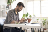 Smiling man using smartphone during lunch break at desk in office - VPIF01800