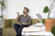Smiling man sitting on couch in office playing with a tennis ball - VPIF01803