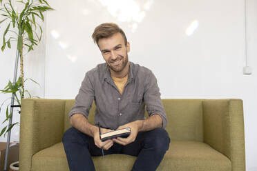 Portrait of smiling man sitting on couch with a book - VPIF01806