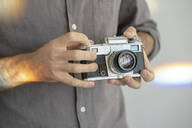 Close-up of man holding old-fashioned camera - VPIF01812