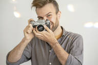 Portrait of smiling man taking picture with an old-fashioned camera - VPIF01815