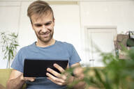 Smiling man sitting on couch using tablet - VPIF01818
