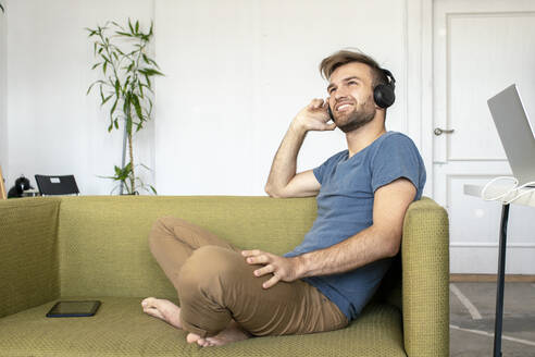 Smiling man sitting on couch in office listening to music - VPIF01821