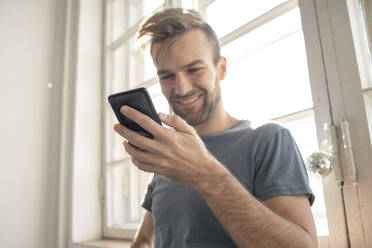 Smiling man using smartphone at the window - VPIF01824