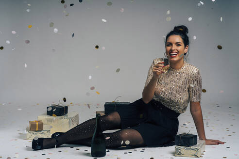 Portrait of young woman dressed for a party, celebrating Christmas with gifts and champagne - MPPF00298