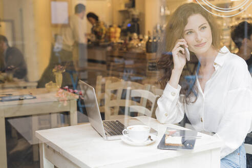Woman on the phone in a cafe - FMOF00762