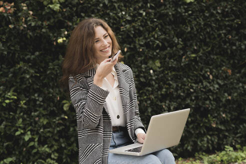 Smiling woman using smartphone and laptop outdoors - FMOF00771