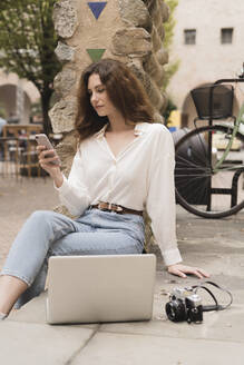 Young woman with smartphone, camera and laptop outdoors - FMOF00786