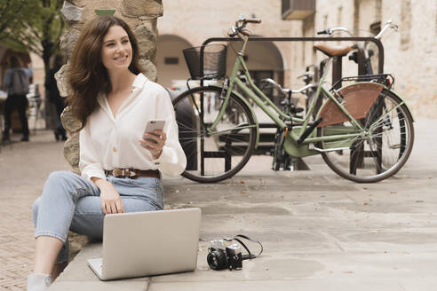Smiling young woman with smartphone, camera and laptop outdoors - FMOF00789