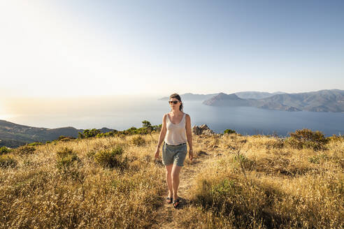 Female hiker during hike, Belvedere de Saliccio, Piana, Corse-du-Sud, Corsica, France - MSUF00015