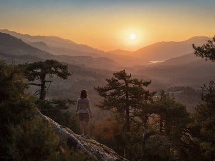 Female hiker standing on viewpoint, Albertacce, Lac de Calacuccia at sunrise, Haute-Corse, Corsica, France - MSUF00036