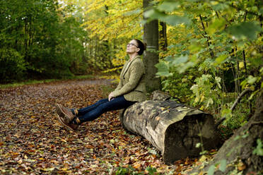 Mature woman sitting on a tree trunk in a autumn forest - FLLF00352