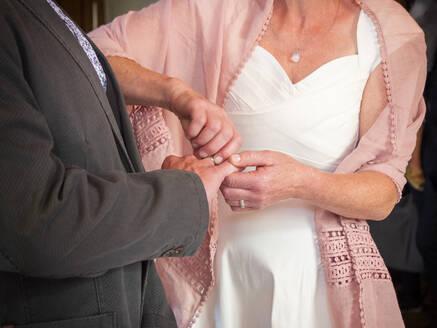 Bride putting wedding ring on finger of groom - LAF02427