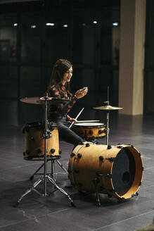 Smiling female drummer using her smartphone - MTBF00218
