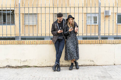 Young couple in the city using their mobile phones - ERRF02165