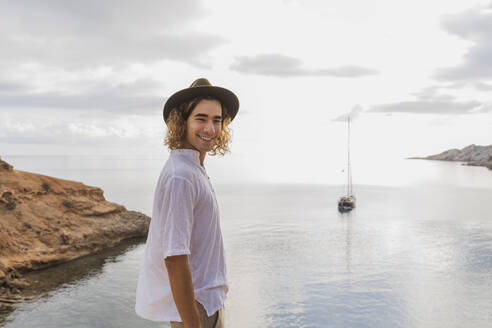 Portrait of relaxed young man in front of the sea, Ibiza, Balearic Islands, Spain - AFVF04250