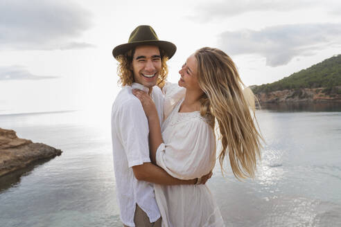 Portrait of young couple in love standing in front of the sea, Ibiza, Balearic Islands, Spain - AFVF04256
