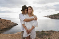 Portrait of young couple in love standing in front of the sea with eyes closed, Ibiza, Balearic Islands, Spain - AFVF04259