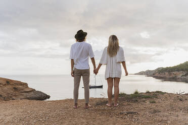 Back view of young couple in love standing in front of the sea, Ibiza, Balearic Islands, Spain - AFVF04265