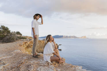 Young couple in front of the sea looking at distance, Ibiza, Balearic Islands, Spain - AFVF04271