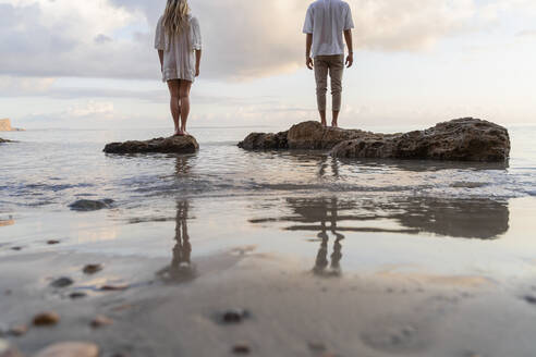 Back view of young couple standing on rocks in front of the sea, Ibiza, Balearic Islands, Spain - AFVF04277