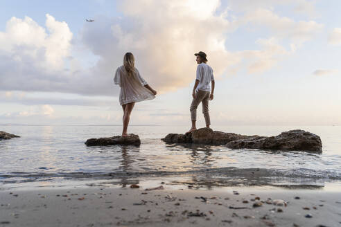 Back view of young couple standing on rocks in front of the sea, Ibiza, Balearic Islands, Spain - AFVF04280