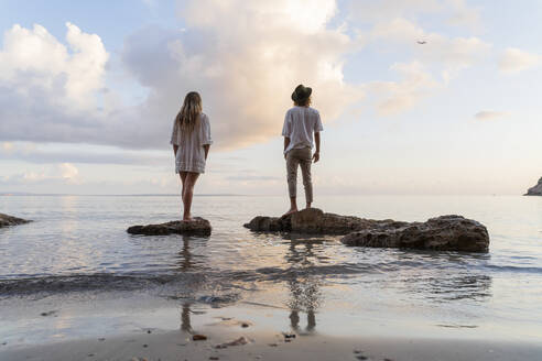 Back view of young couple standing on rocks in front of the sea watching airplane, Ibiza, Balearic Islands, Spain - AFVF04283