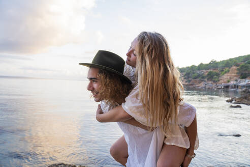 Young man giving his girlfriend a piggyback ride in front of the sea, Ibiza, Balearic Islands, Spain - AFVF04286
