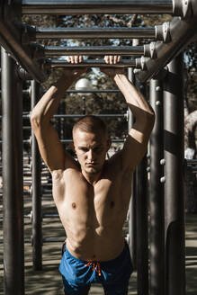 Barechested muscular man practicing fitness exercises at climbing frame - RCPF00127