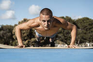 Portrait of barechested muscular man doing pushups outdoors - RCPF00130