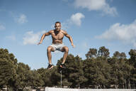 Portrait of barechested muscular man jumping outdoors - RCPF00133