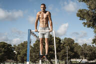 Barechested muscular man practicing fitness exercises on football goal outdoors - RCPF00139
