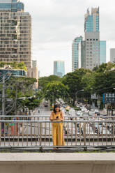 Fashionable woman dressed in yellow standing on a bridge looking at cell phone, Bangkok, Thailand - MAUF03134