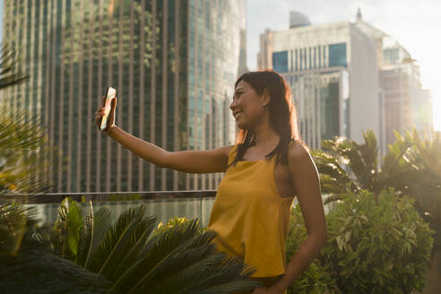 Smiling woman standing on roof terrace in the evening taking selfie with smartphone, Bangkok, Thailand - MAUF03137