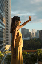Woman standing on roof terrace watching sunset, Bangkok, Thailand - MAUF03143
