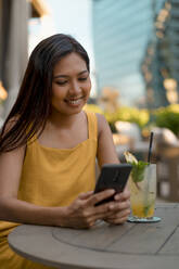 Portrait of smiling woman sitting in a cafe looking at cell phone - MAUF03149
