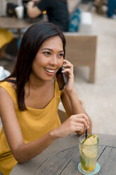 Portrait of smiling woman on the phone sitting in a cafe with a drink - MAUF03152