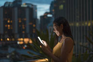 Smiling woman standing on roof terrace at dusk looking at cell phone, Bangkok, Thailand - MAUF03158