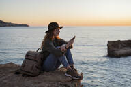 Young woman using smartphone on beach during sunset, Ibiza - AFVF04289