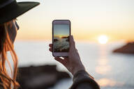 Young woman using smartphone on beach during sunset, Ibiza - AFVF04292