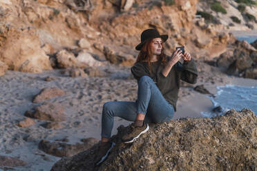 Young woman using smartphone on beach during sunset, Ibiza - AFVF04298