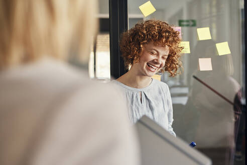 Laughing businesswoman with sticky notes at glass pane in office - ZEDF02733