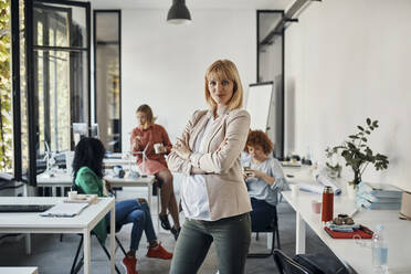 Portrait of confident pregnant businesswoman in office with colleagues in background - ZEDF02784